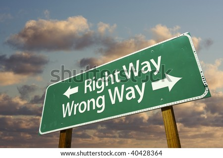 Right and Wrong Way Green Road Sign with dramatic blue sky and clouds. - stock photo