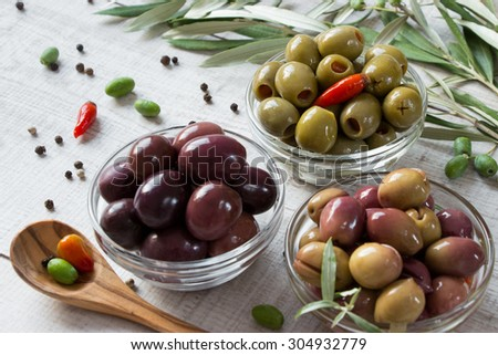 Right 3 bowls with kind of olives green olives, black olives, green olives stuffed with pepper framed by olive tree branches and scattered peppercorns . 3 types of olives. Horizontal shot.Daylight.    - stock photo