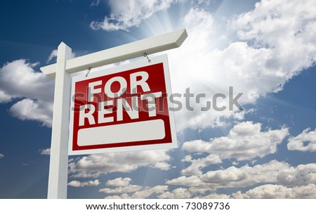 Right Facing For Rent Real Estate Sign Over Clouds and Sunny Sky with Room For Text. - stock photo