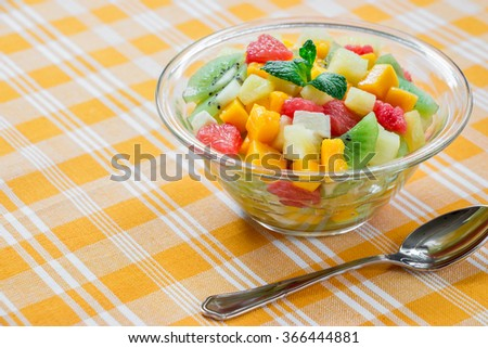 Right glass bowl with fruit salad of mango, pineapple, grapefruit, banana and kiwi, left empty space on yellow checkered tablecloth. Fruit exotic salad with spoon close. Daylight. Horizontal.