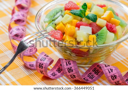 Right glass bowl with fruit salad of mango, pineapple, grapefruit, banana and kiwi, left pink centimeter on yellow checkered tablecloth. Fruit exotic salad with fork, centimeter. Daylight. Horizontal. - stock photo