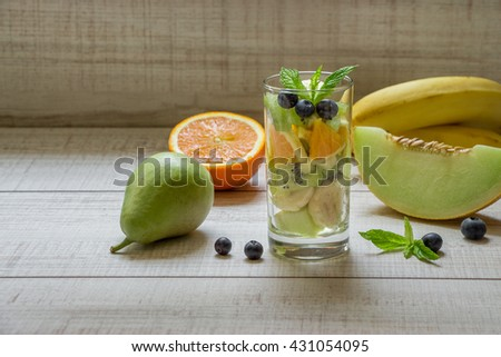 Right glass with sliced fruits melon, banana, orange, kiwi, pear next to ingredients, left empty space for text also in frame blueberries, mint on light background. Glass of fruit salad. Horizontal.