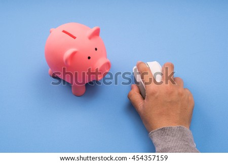 right hand click mouse computer and piggy coin saving, blue background. - stock photo