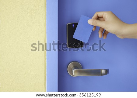 right hand hold key card touch on black electronic pad lock access control with stainless steel door handle on blue door - stock photo