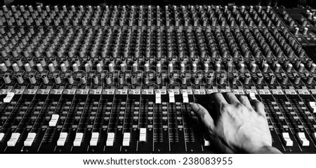 right hand of sound engineer working on recording studio mixer. bw filter