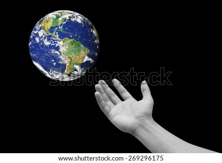 Right hand palm gesture reaching the colorful earth isolated on black backgrounds. Elements of this image furnished by NASA - stock photo
