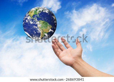 Right hand palm gesture with earth on blue sky backgrounds. Elements of this image furnished by NASA - stock photo