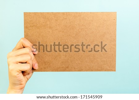 Right hand showing a blank cardboard message - stock photo