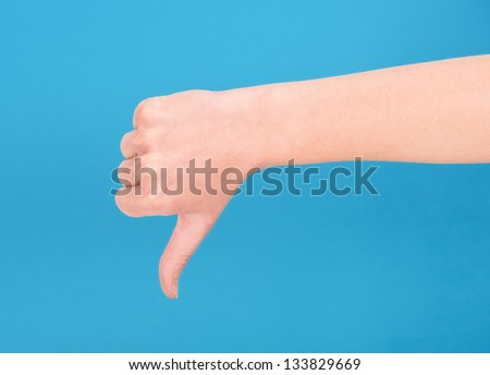 Right hand showing thumb down on blue background - stock photo