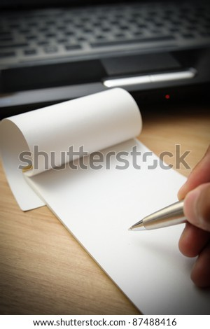 right hand take a note on blank paper with office environment