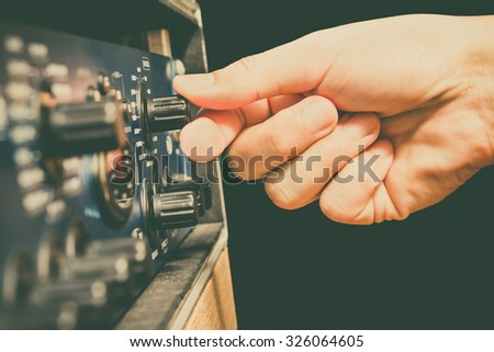right hand tuning knobs of studio gears, pre-amp, audio interface, effect signal processor isolated on black + art filter for TV radio broadcasting, post production or music concept - stock photo