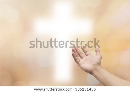 right hands praying on blurred white cross on golden background:humans hand open gesture reaching and receiving power from cross. religion concept :faith and strength and forgiveness conceptual. - stock photo