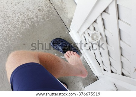 Right leg of a mature male wearing blue sports shorts rinsing sand from his foot after visiting the beach. Outdoor water spigot spraying sand off a mans right foot outdoors