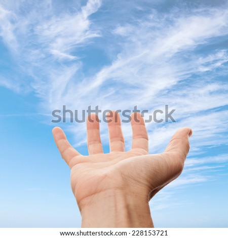 Right male hand with empty place for holding something, on blue sky background. Photo with selective focus - stock photo