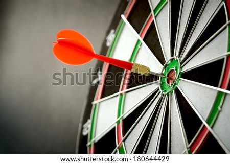 Right on target concept using dart in the bullseye on dartboard - stock photo