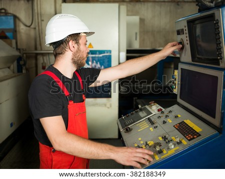 right side close-up of a man wearing red overalls and a white protective helmet, standing, operating the control panel of an industrial machinery, in an industrial hall - stock photo