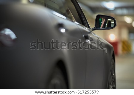 Right side of modern car at underground parking, focus on rear view mirror.