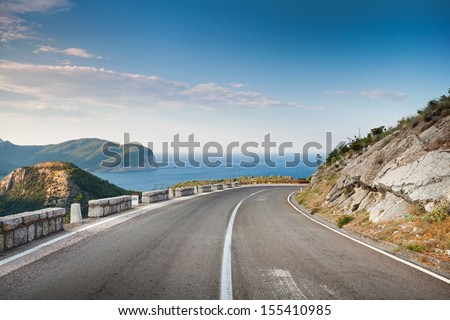 Right turn of mountain highway with blue sky and sea on a background - stock photo