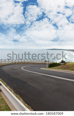 Right turn of mountain road near the sea under blue sky