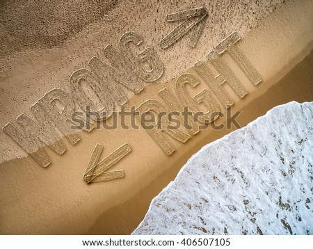 Right - Wrong written on the beach - stock photo