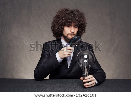 rigorous businessman examining a huge bulb carefully with a magnifying glass on grunge background - stock photo