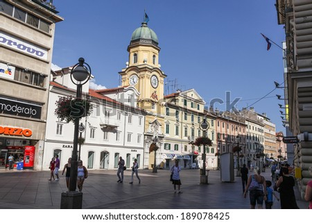 RIJEKA, CROATIA - AUGUST 7, 2012: Pedestrian zone in Rijeka with 19th century Baroque clock tower and people walking up and down the street. Rijeka is the third-largest city in Croatia - stock photo