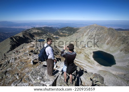 Rila, Bulgaria - September 8, 2012: A man is photographing the Musala lakes from the rocky hills of Rila mountain.