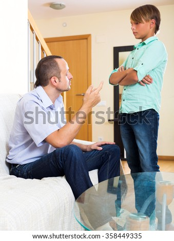 Riley father and teenage son discussing something interesting indoors. Focus on the man - stock photo