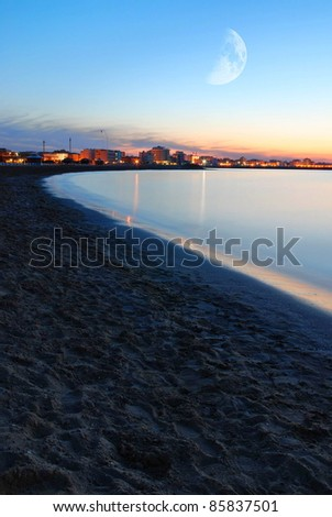 rimini waterfront in the evening with moon in the sky - stock photo