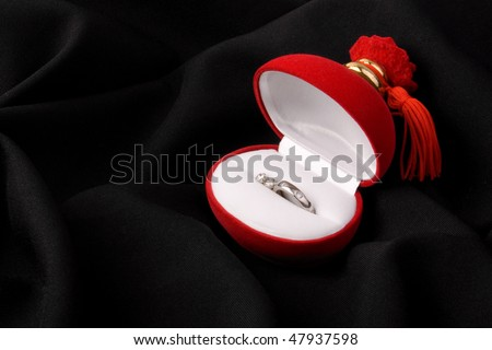 Ring and ear rings in red box on black background - stock photo