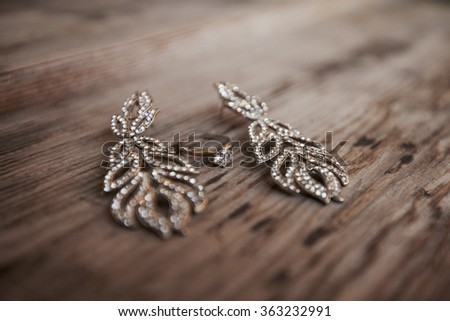 ring and earrings on a wooden table - stock photo