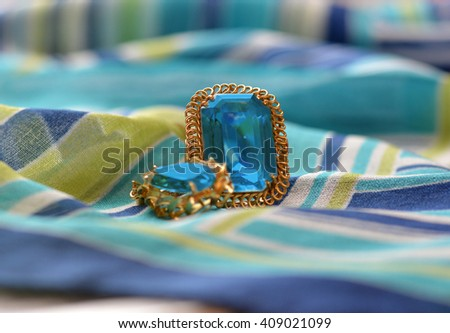 ring and necklace golden accompanied by a precious stone  - stock photo