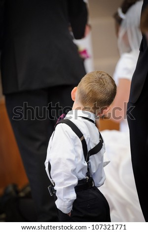 Ring bearer looking at the bride and groom - stock photo