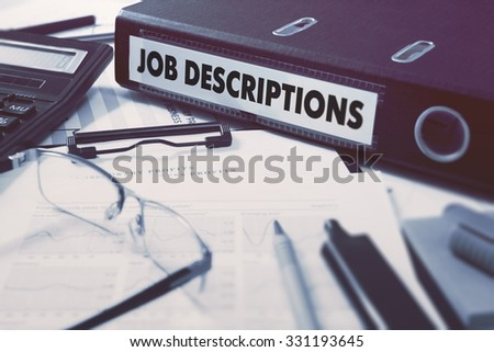 Ring Binder with inscription Job Descriptions on Background of Working Table with Office Supplies, Glasses, Reports. Toned Illustration. Business Concept on Blurred Background. - stock photo