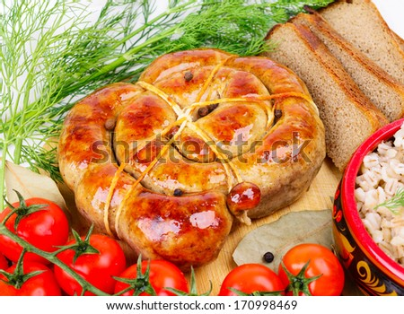 Ring bratwurst bread with tomatoes and herbs. - stock photo