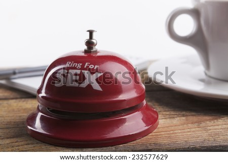Ring for sex bell on wood table with coffee and notepad in the background - stock photo