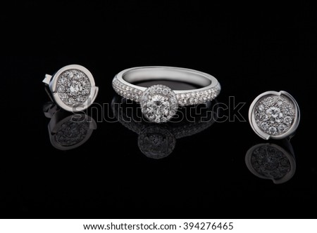 Ring from white gold and an earring with jewels on a black background - stock photo