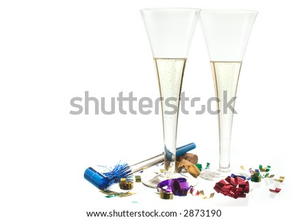 Ring in the New Year with a champagne toast! Two champagne flutes with confetti and a noisemaker on white ground with some reflection.