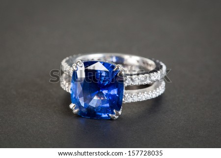 Ring of the jeweler with dark blue sapphire on the black background - stock photo