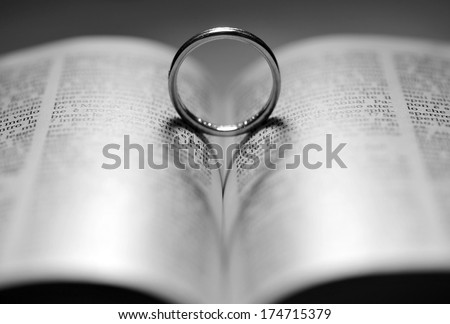 Ring on the bible with backlight form heart - stock photo