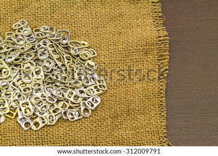 Ring pull aluminum of cans aluminum plastic use for prostheses in  brown sack fabric  on black wooden background - stock photo