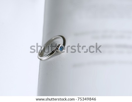 ring with blue stone in an open book