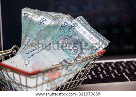 Ringgit Malaysia in shopping cart trolley with keyboard notebook as background. Malaysia currency having a currency crisis in year 2015 due to market oil price  - stock photo