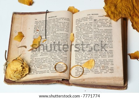 rings and faded flower on the old holy bible - stock photo