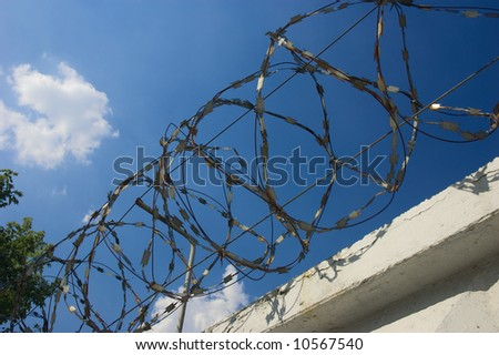 Rings of barbed wire on top fence - stock photo
