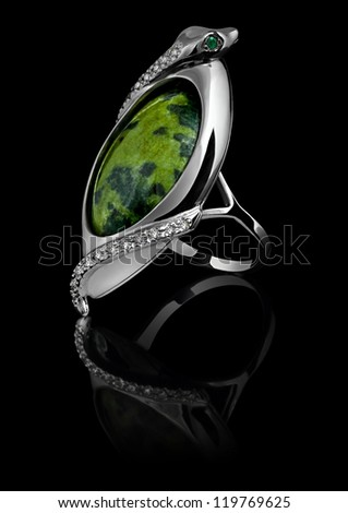 Rings with diamonds and green gem isolated on black background