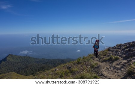 RINJANI MOUNTAIN, LOMBOK, INDONESIA-JUNE 11,2015: Mountain guide AB Pramono with trekking pole walks slowly on trekking path on the way to Rinjani Mountain in Lombok, Indonesia. - stock photo