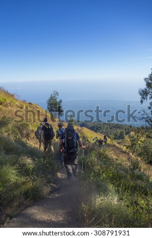 RINJANI MOUNTAIN, LOMBOK, INDONESIA-JUNE 11,2015: Unidentified hikers or trekkers walks slowly on trekking path on the way back from Rinjani Mountain in Lombok, Indonesia. - stock photo