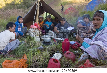 RINJANI MOUNTAIN, LOMBOK, INDONESIA-JUNE 10,2015: Unidentified mountain porters prepare food for trekkers on their way climb Rinjani Mountain in Lombok, Indonesia. - stock photo