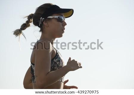 RIO DE JANEIRO - APRIL 3, 2016: Carioca Brazilian woman jogs along the Copacabana beachfront, a common sight in a city well-known for its fitness fanatics.  - stock photo